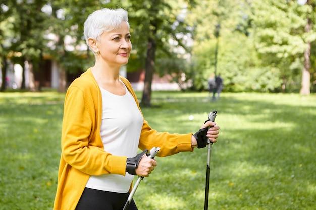 성숙한 사람, 노화, 스포츠 및 웰빙 개념. 은퇴에 건강한 활동적인 라이프 스타일을 선택하는 아름다운 세련된 노인 여성, 야외에서 아침을 보내고, 스칸디나비아 걷기를 즐기고