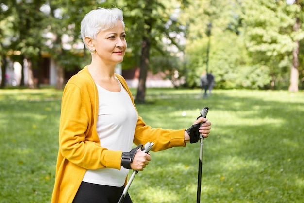 Mature people, aging, sports and well-being concept. beautiful stylish elderly woman choosing healthy active lifestyle on retirement, spending morning outdoors, enjoying scandinavian walking