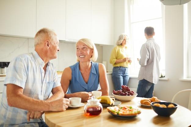 Зрелые люди пьют чай на кухне