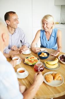Зрелые люди наслаждаются обедом и чаем