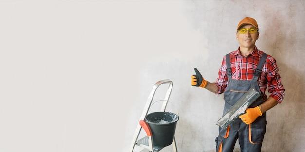 벽 근처에서 엄지손가락을 위로 보여주는 성숙한 미장공. 건설 작업 개념의 hight 품질입니다.