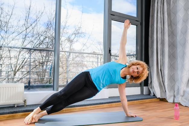 Зрелая позитивная женщина в спортивной одежде стоит на одной руке и ногами на спортивном коврике
