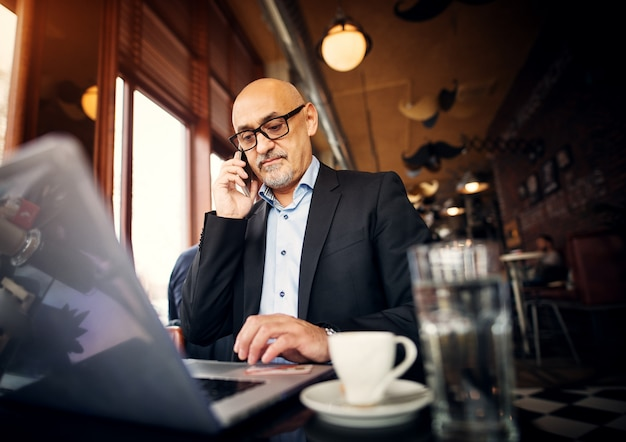 Mature professional businessman is sitting at the table of the coffee shop making a phone call and using a laptop