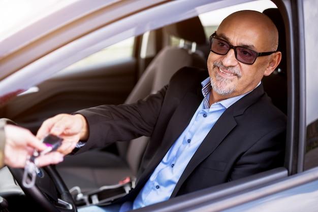成熟したプロのエレガントな幸せな成功したビジネスマンは、車の購入に成功した後、車の中に座っている間キーを取っています。