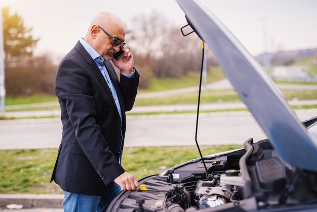 Mature professional elegant stressed businessman in the suit is looking under the cars hood and is phone calling tow truck.