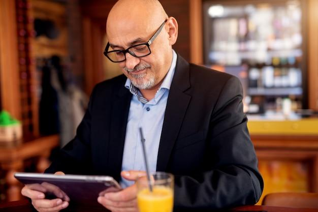 成熟した専門家に焦点を当てたビジネスマンは、コーヒーショップでタブレットとジュースを飲んでいます。