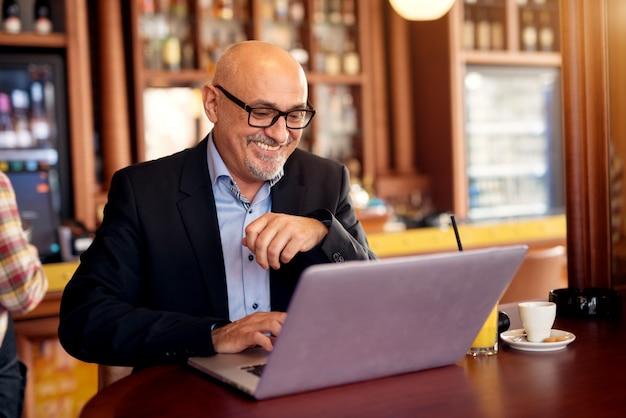 成熟したプロの幸せなビジネスマンは、ラップトップを使用して、コーヒーショップでコーヒーを飲みます。