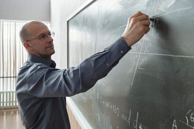 Зрелый профессор университета в элегантной повседневной одежде стоит перед доской на уроке в аудитории и записывает формулу