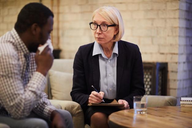 Mature psychiatrist listening to patient