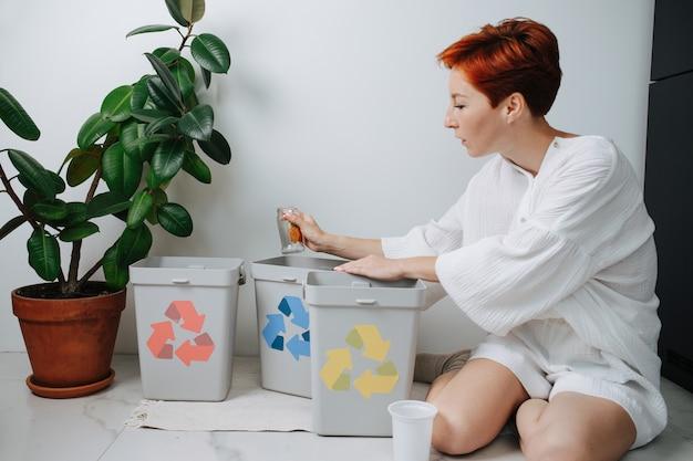 Зрелая рыжеволосая женщина сидит на ногах, сортируя мусор между небольшими мусорными баками у себя дома. на них нанесены стрелки разного цвета. держит стеклянную банку.