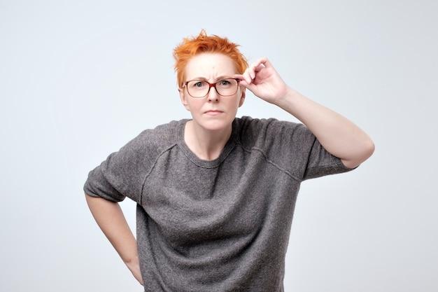 灰色のブラウスで成熟した赤毛の女性