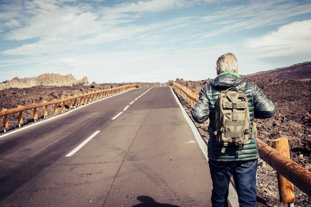 後ろから見た成熟した引退した男は、緑のバックパックで山の砂漠の真ん中にある長くまっすぐなアスファルト道路を歩きます-大人のための独立と孤独な旅行者のコンセプトをお楽しみください
