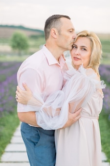 라벤더 밭을 걷고 있는 성숙한 낭만적인 사랑의 커플.
