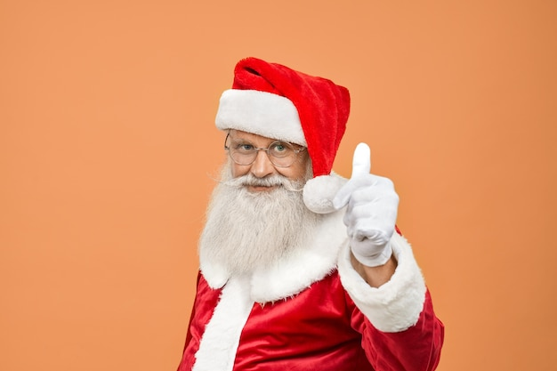 Mature santa claus in traditional costume with real grey beard and eyeglasses showing thumb up