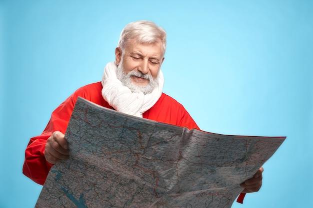 Babbo natale maturo con mappa cartacea che pianifica il giorno di natale