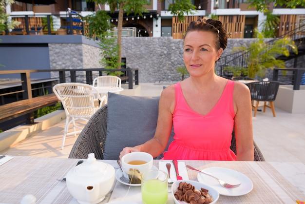 리조트에서 야외에서 아침을 먹고 성숙한 스칸디나비아 관광 여자
