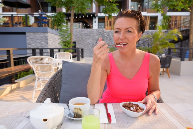 リゾートで屋外で朝食をとる成熟したスカンジナビアの観光客の女性