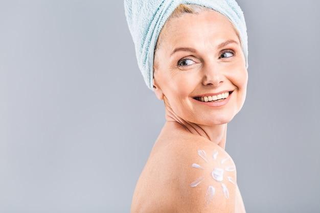 太陽の形をした日焼け止めクリームと成熟した年配の美しい女性。日焼け治療の準備ができているきれいな女性。女性の肩に描く日焼け止めローションの太陽。白い背景で隔離。