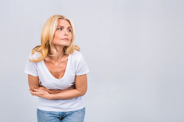 Mature senior blonde woman in casual with a stomachache isolated on a gray white background. strong pain in stomach.