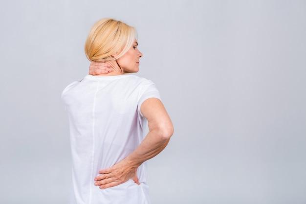 Зрелая старшая старая красивая женщина, носящая случайные страдания от боли в спине. пустое пустое пространство копии с концепцией боли в спине. изолированные на белом сером фоне