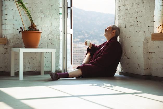 Uomo anziano anziano maturo durante la quarantena, rendendosi conto di quanto sia importante rimanere a casa durante l'epidemia di virus