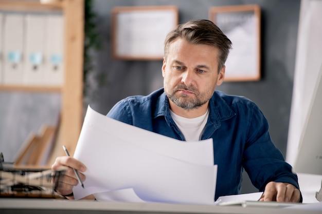カジュアルな服装で成熟した真面目な建築家、オフィスでの勤務中にデスクでスケッチをチェック