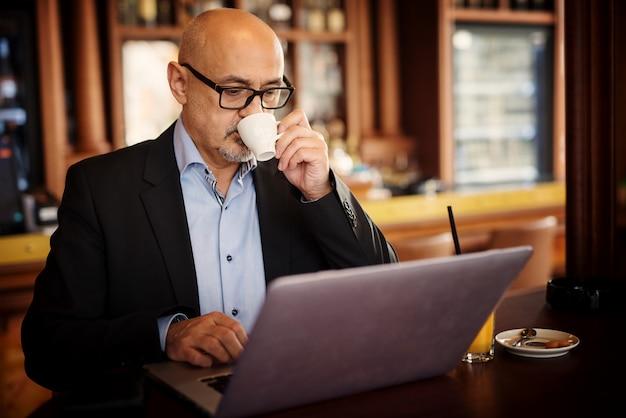 成熟した真面目な実業家は、ラップトップを使用して、コーヒーショップのテーブルに座っている間、彼のコーヒーのカップから一口を取っています。