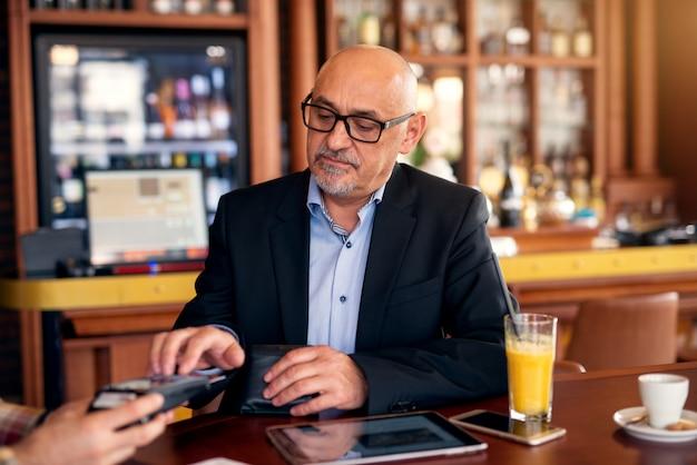 成熟した深刻なプロのビジネスマンは、コーヒーショップに座っている間、タブレットを使用してクレジットカードで小切手を支払う。