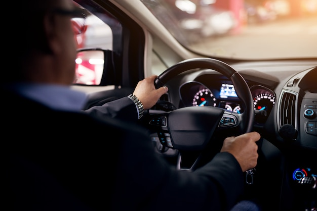 Зрелые серьезные профессиональный элегантный бизнесмен в костюме за рулем автомобиля в ночное время.