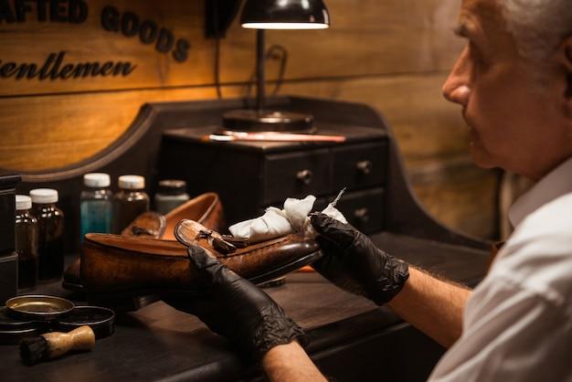Calzolaio maturo in officina che fa le scarpe