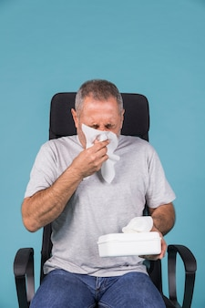 Mature sick man blowing his nose with tissue