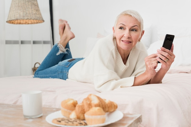 Mature smiley woman in bed holding smartphone
