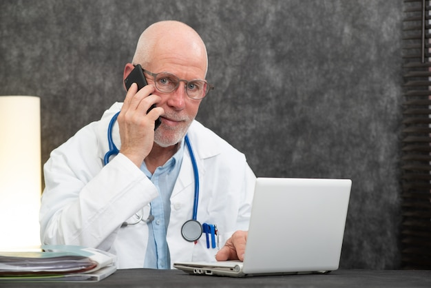 Mature smiling bearded doctor talking on phone