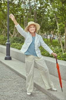 Mature smiling european woman tourist in wicker hat and stylish clothes waves to someone in public park.