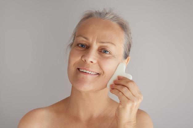 회색 배경에 격리된 옥 판자로 얼굴을 마사지하는 성숙한 미소 백발의 여성