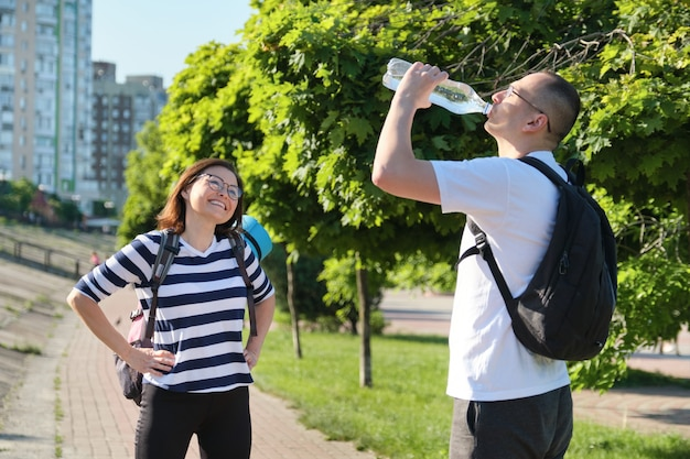 Зрелые улыбающиеся мужчина и женщина в спортивной одежде с рюкзаками и ковриком для упражнений гуляют в городском парке, разговаривают и пьют воду из бутылки