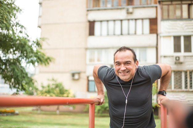 Mature smiling man is training on the uneven bars