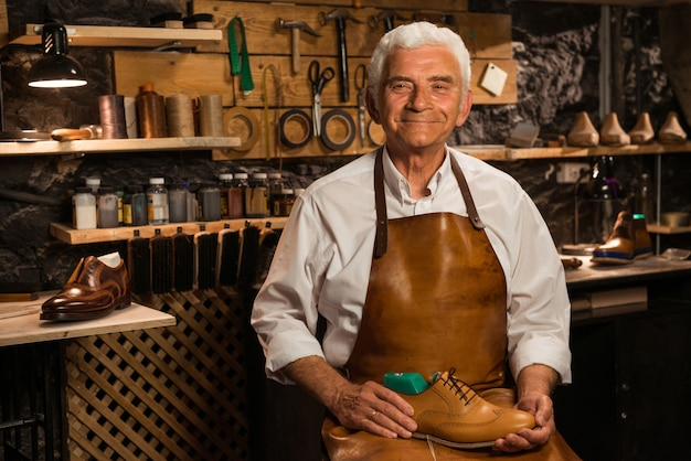Mature smiling shoemaker in workshop holding shoes
