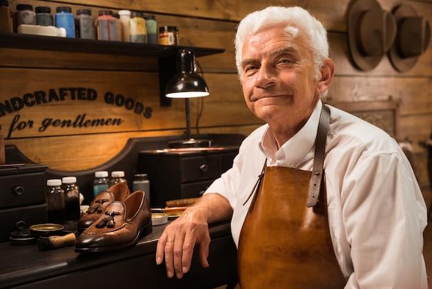 Mature smiling shoemaker in workshop making shoes