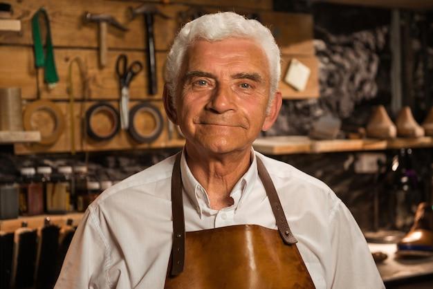 Mature smiling shoemaker in workshop