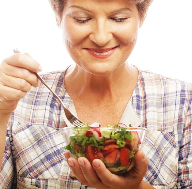 サラダを食べる成熟した笑顔の女性。白で隔離。
