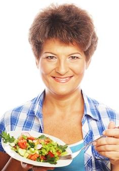 サラダを食べる成熟した笑顔の女性
