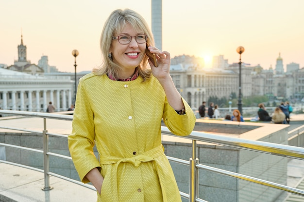 Mature smiling woman in glasses, yellow coat talking on mobile phone