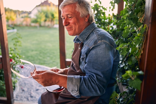 Mature sommelier in a winery garden sitting alone and looking at the empty glass after drinking wine