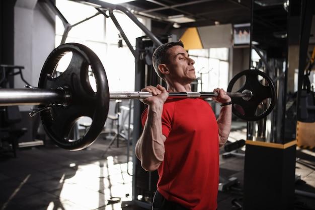 スポーツスタジオで重いバーベルで運動する成熟したスポーツマン