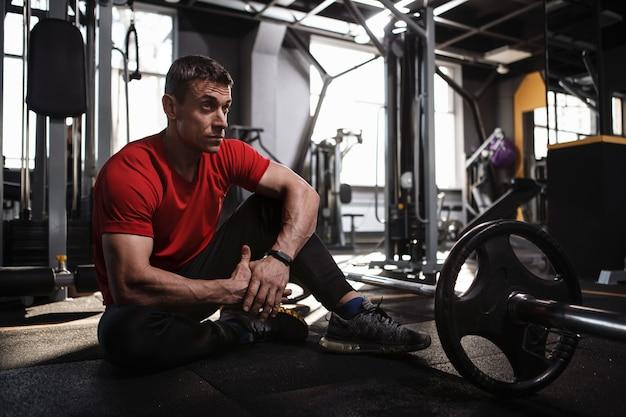 重いバーベル、コピースペースで運動した後、体育館の床で休んでいる成熟したスポーツマン