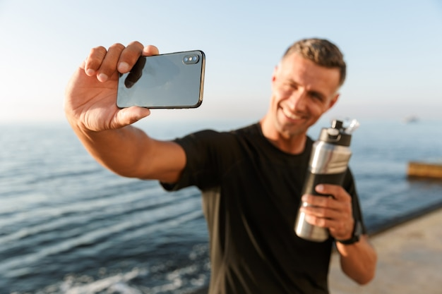 成熟したスポーツマンは、ビーチでボトル入り飲料水で自分撮りをします。