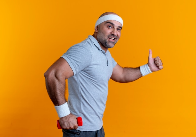 Maturo uomo sportivo in fascia tenendo il manubrio guardando in avanti sorridendo allegramente mostrando i pollici in su in piedi sopra la parete arancione