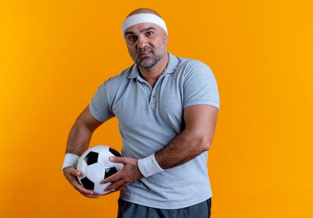 Maturo uomo sportivo in fascia tenendo il pallone da calcio guardando in avanti con la faccia seria in piedi sopra la parete arancione