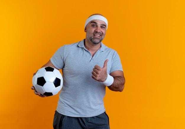 Maturo uomo sportivo in fascia tenendo il pallone da calcio guardando in avanti con il sorriso sul viso che mostra i pollici in su in piedi sopra la parete arancione